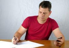 Scrittura del giovane su una carta fotografie stock