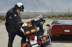 Scrittura del poliziotto di traffico contro il motociclo Immagini Stock