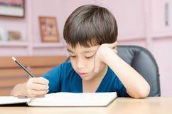 Scrittura del ragazzino e compito di pensiero Fotografie Stock Libere da Diritti