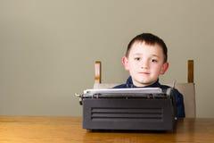 Scrittura del ragazzino su un vecchio sorridere della macchina da scrivere Immagini Stock Libere da Diritti