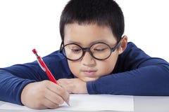 Scrittura del ragazzino sulla carta Fotografia Stock Libera da Diritti