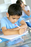 Scrittura del ragazzino in taccuino Fotografia Stock
