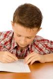 Scrittura del ragazzo di banco Immagini Stock Libere da Diritti