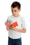 Scrittura del ragazzo di banco in libro Fotografie Stock Libere da Diritti