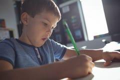 Scrittura del ragazzo in libro sullo scrittorio all'aula Immagini Stock Libere da Diritti