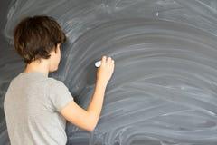 Scrittura del ragazzo sul bordo nero Fotografia Stock Libera da Diritti