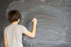Scrittura del ragazzo sul bordo nero Immagini Stock Libere da Diritti