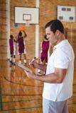 Scrittura dell'allenatore di pallacanestro sulla lavagna per appunti Immagine Stock