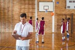 Scrittura dell'allenatore di pallacanestro sulla lavagna per appunti Fotografia Stock Libera da Diritti