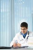 Scrittura dell'allievo o del medico all'ufficio Fotografie Stock