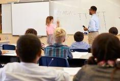 Scrittura dell'allievo sul bordo in una lezione della scuola elementare Fotografie Stock Libere da Diritti