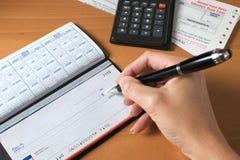 Scrittura dell'assegno per pagare le fatture, penna di holding della mano Fotografie Stock Libere da Diritti