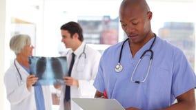 Scrittura dell'infermiere su una lavagna per appunti davanti a medici archivi video