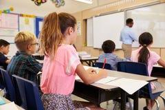 Scrittura dell'insegnante sul bordo in una classe della scuola elementare Immagine Stock Libera da Diritti
