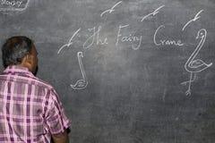 Scrittura dell'insegnante dell'uomo sulla lavagna all'aula Immagini Stock
