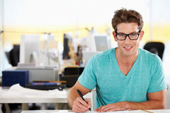 Scrittura dell'uomo allo scrittorio in ufficio creativo occupato Immagini Stock