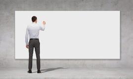Scrittura dell'uomo d'affari con l'indicatore sul bordo bianco Immagine Stock