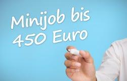 Scrittura dell'uomo d'affari con un euro della Banca dei Regolamenti Internazionali 450 del minijob dell'indicatore Fotografia Stock Libera da Diritti