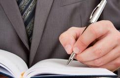 Scrittura dell'uomo d'affari in diario di affari Fotografia Stock Libera da Diritti