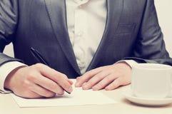Scrittura dell'uomo d'affari su un documento Fotografia Stock