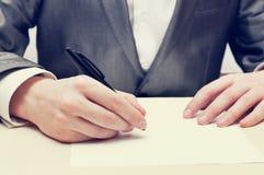 Scrittura dell'uomo d'affari su un documento Fotografie Stock