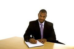 Scrittura dell'uomo di colore allo scrittorio che esamina macchina fotografica Immagine Stock
