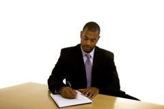 Scrittura dell'uomo di colore allo scrittorio che osserva giù immagini stock
