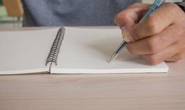 Scrittura dell'uomo sul taccuino Immagine Stock