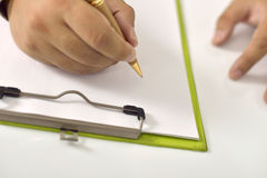 Scrittura dell'uomo sulla carta in bianco sulla lavagna per appunti Fotografie Stock Libere da Diritti