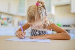 Scrittura della bambina con la penna in taccuino Immagini Stock