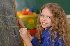 Scrittura della bambina sulla lavagna Fotografia Stock Libera da Diritti