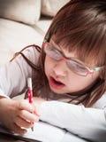 Scrittura della bambina in suo taccuino Immagini Stock