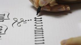 Scrittura della calligrafia gotica la mano femminile scrive con la penna stock footage