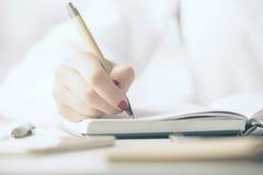 Scrittura della donna in blocchetto per appunti Fotografia Stock