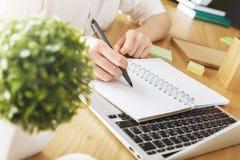 Scrittura della donna di affari in blocco note Fotografia Stock