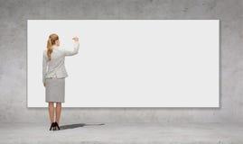 Scrittura della donna di affari con l'indicatore sul bordo bianco Immagini Stock