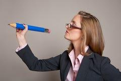 Scrittura della donna di affari con la matita gigante Immagini Stock