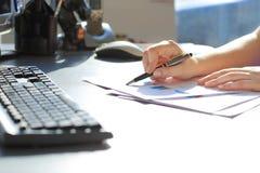 Scrittura della donna di affari con la penna Fotografie Stock Libere da Diritti