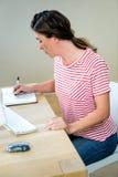 scrittura della donna di affari nel suo pianificatore Immagine Stock