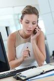 Scrittura della donna di affari nell'ordine del giorno e parlare sul telefono Immagine Stock