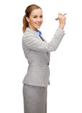 Scrittura della donna di affari qualcosa in aria con l'indicatore Immagine Stock
