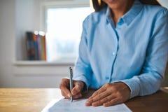 Scrittura della donna di affari su un documento Fotografie Stock