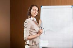 Scrittura della donna di affari sul flipchart Fotografie Stock