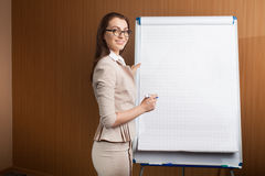 Scrittura della donna di affari sul flipchart Immagini Stock Libere da Diritti