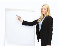 Scrittura della donna di affari sul flipchart in ufficio Immagine Stock Libera da Diritti