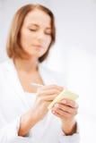 Scrittura della donna di affari sulla nota appiccicosa Fotografia Stock Libera da Diritti