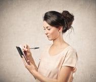 Scrittura della donna sul suo taccuino Fotografia Stock