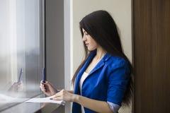 Scrittura della donna sulla carta che sta finestra vicina immagine stock libera da diritti