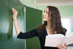 Scrittura della donna sulla lavagna all'aula Immagini Stock Libere da Diritti