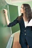 Scrittura della donna sulla lavagna all'aula Fotografia Stock
